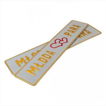 Tablice ślubne, aluminiowe, tłoczone. Tablice w kolorze białym ze złotym napisem Młoda Para, Serce umiejscowione na środku w czerwonym kolorze.