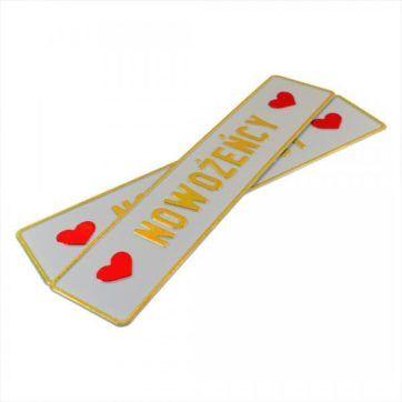 Tablice ślubne, aluminiowe, tłoczone. Tablica w kolorze białym ze złotym napisem Nowożeńcy. Serca po bokach w kolorze czerwonym.